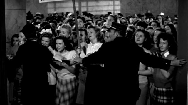 two guards open a gate and hold back a crowd of fanatical bobby soxers in a train station. - 1944 stock videos & royalty-free footage