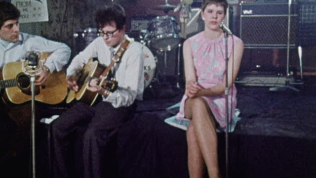 vídeos de stock, filmes e b-roll de montage two guitarists and a singer performing a folk song for off-duty nurses / plymouth, england, united kingdom - 1969