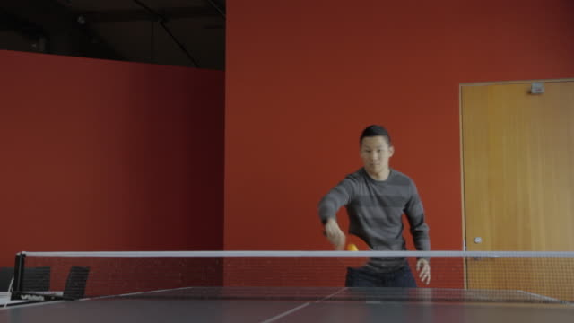 vídeos de stock, filmes e b-roll de two guys attempting to play ping pong from table view - tênis de mesa