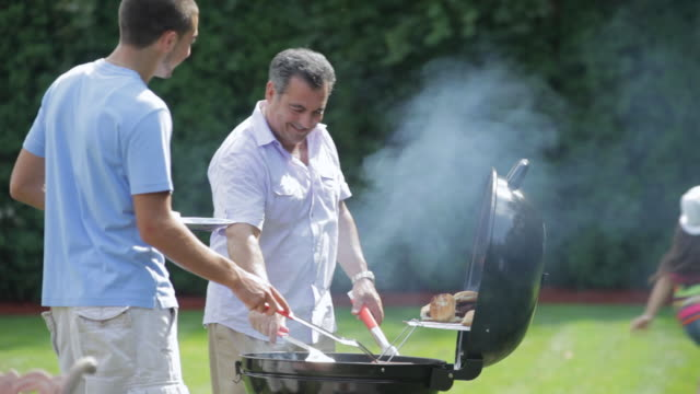 ms two guys cooking at family picnic / east hanover, new jersey, united states - gegrillt stock-videos und b-roll-filmmaterial