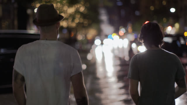 Two guys walk through downtown Austin at night