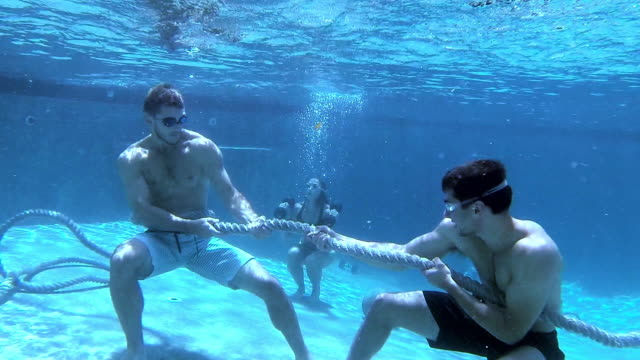 two gym athletes do a tug of war workout underwater in a pool