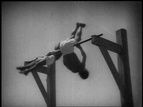 1939 montage two gymnasts on high bar on the beach, spinning and jumping off with other children in the background / japan - sbarra da ginnastica video stock e b–roll