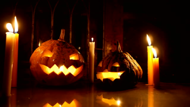 two halloween pumpkins jack-o-lantern with candles on glass in the night, dolly shot - conceptual symbol stock videos and b-roll footage