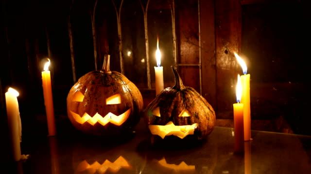 vídeos y material grabado en eventos de stock de dos calabazas de halloween gato-o-linterna con velas en cristal en la noche, tiro de carro - calabaza no comestible