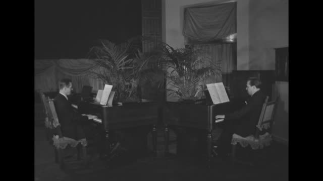 ws two hammond organs stand on stage at an angle to each other potted palms stand behind them organists harry campbell and gordon seaman play a duet... - music stand stock videos and b-roll footage