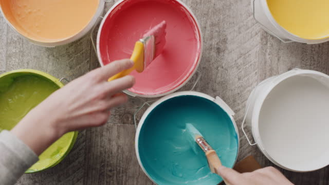 two hands taking paint from bucket with paintbrush - restoring stock videos & royalty-free footage