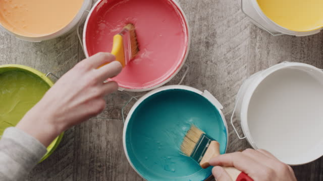 two hands taking paint from bucket with paintbrush - bucket stock videos & royalty-free footage