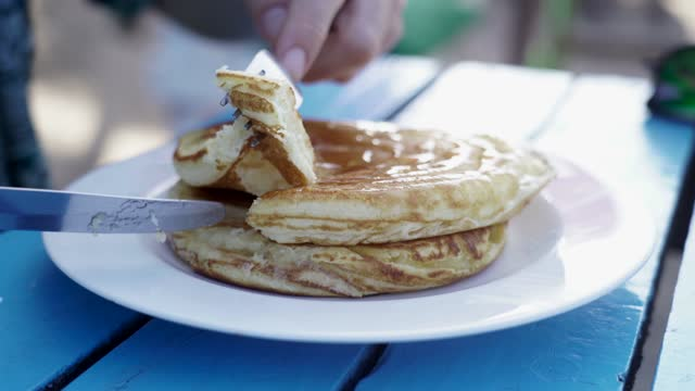 two hands using fork and knife to cut some thai pancakes on blue table - porous stock videos & royalty-free footage