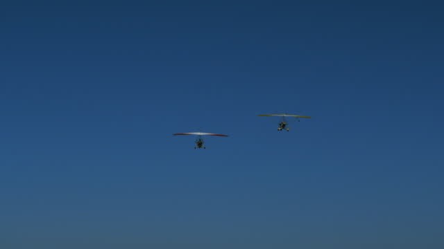 two hang gliders flying towards a runway - hang gliding stock videos and b-roll footage