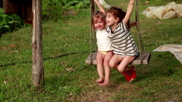 two happy little girl swinging on the rope swings in the backyard - rope swing stock videos & royalty-free footage