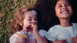 Two happy little girls smiling lying on grass being tickled