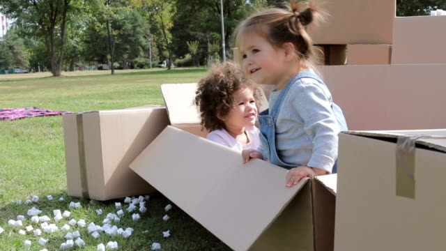 two happy multicultural babies playing in cardboard boxes, one baby is getting nervous and wants to get out, done with playing - polystyrene stock videos & royalty-free footage