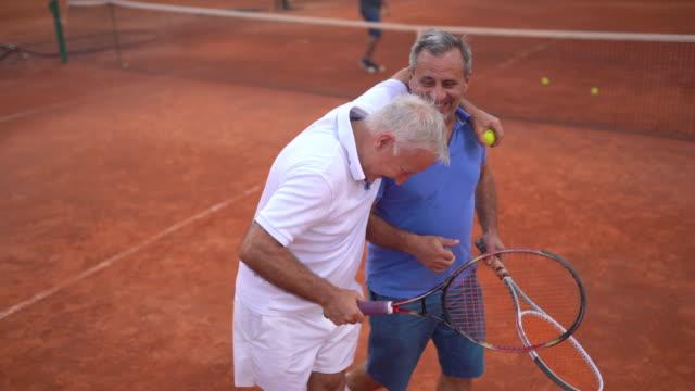 vídeos de stock, filmes e b-roll de dois amigos veteranos felizes na quadra de tênis - amizade masculina