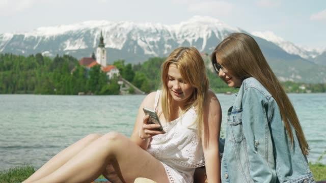 vídeos y material grabado en eventos de stock de dos chicas felices sonriendo tomando una foto, lago bled en el fondo - hacer un descanso