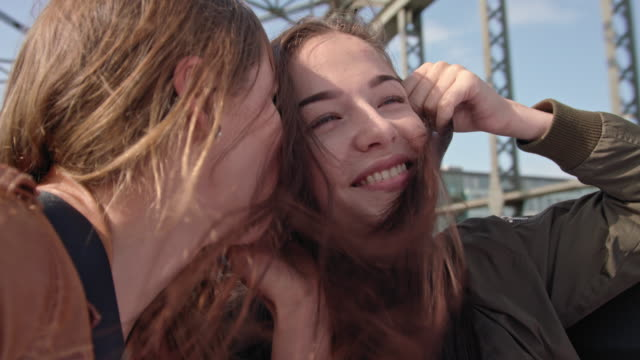 two happy student girls sitting in the back of a convertible while driving over a bridge (hackerbrücke - munich) - part of a series stock-videos und b-roll-filmmaterial