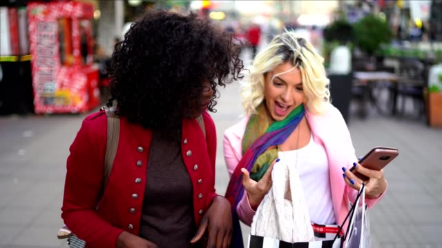 two happy women on the street show to each other what they bought - young couple stock videos & royalty-free footage
