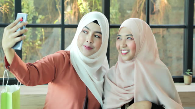 two happy young muslim woman take self portrait with handphone.arab youth - middle eastern culture stock videos & royalty-free footage