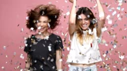 Two happy young women throwing sparkling confetti and dancing isolated over pink background