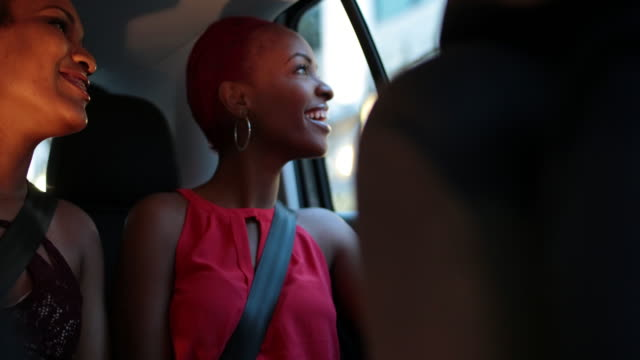 vidéos et rushes de two happy,young woman in back of taxi as it drives through urban area at night. - ceinture de sécurité