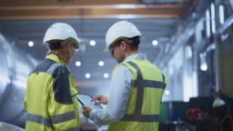 Two Heavy Industry Engineers Stand in Pipe Manufacturing Factory, Use Digital Tablet Computer, Have Discussion. Construction of Oil, Gas and Fuels Transport Pipeline. Back View Sparks Flying