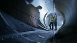 Two Heavy Industry Engineers Walking Inside Pipe, Use Laptop, Have Discussion, Checking Design. Construction of the Oil, Natural Gas and Biofuels Transport Pipeline. Industrial Manufacturing Factory