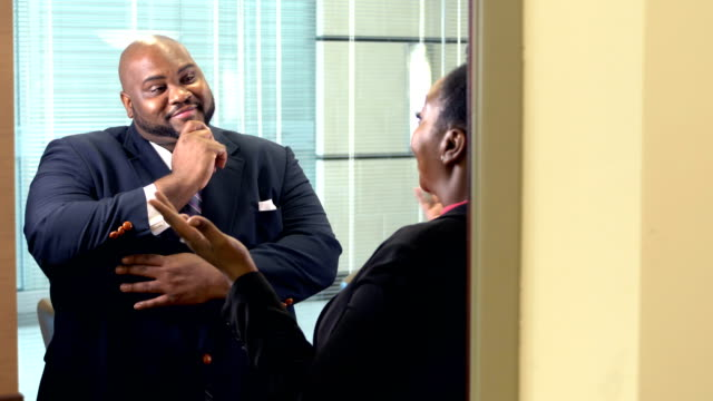 Two heavyset African-American business people talking