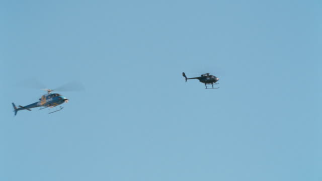 two helicopter fly through the sky. - hovering stock videos & royalty-free footage