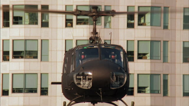 two helicopter pilots fly a helicopter up and over a heliport. - fly swat stock videos & royalty-free footage