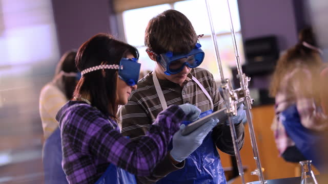 Students share tablets to conduct chemistry lab experiment