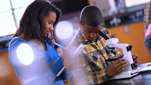 Two students share a microscope, male student peers inside mircorscope, female student takes notes