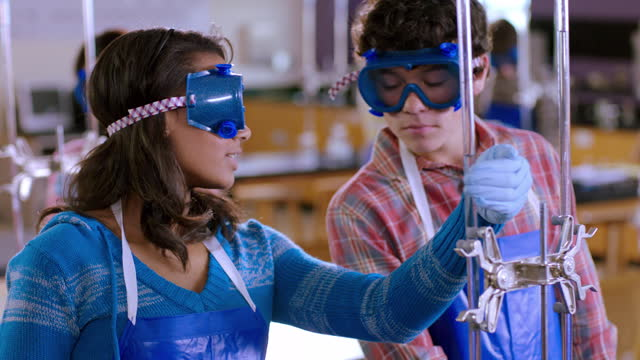 vídeos de stock e filmes b-roll de two high school lab partners take notes and measurements from a burette. - estudar