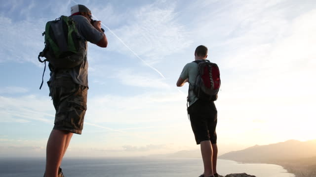 two hikers ascend rock bluff, take pictures - photographing stock videos & royalty-free footage