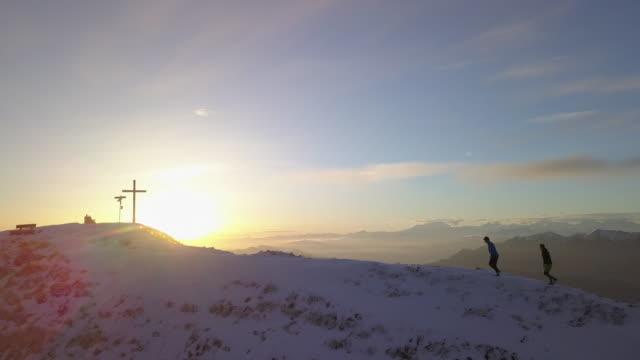 Zwei Wanderer besteigen verschneiten Bergrücken über dem See bei Sonnenuntergang