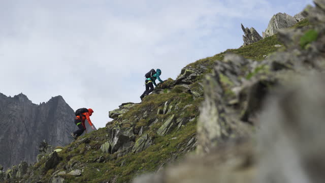 vídeos de stock e filmes b-roll de two hikers climbing up a rocky mountain in cloudy foggy weather - jaqueta jeans
