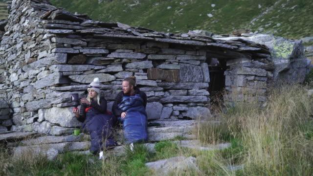 古い石造りの小屋の隣の寝袋で夕食を調理する2人のハイカー - 寝袋点の映像素材/bロール