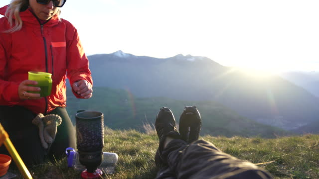 two hikers enjoying a drink in the morning on top of a mountain - young men stock videos & royalty-free footage