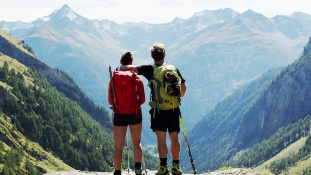 two hikers facing a beautiful mountain vista - austria stock videos & royalty-free footage