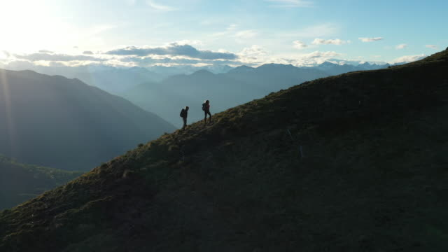 two hikers hiking along a mountain ridgeline - esplorazione video stock e b–roll