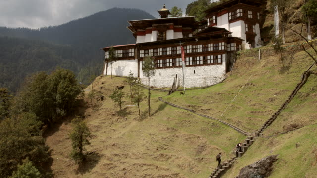 two hikers hiking up to a monastery on a mountain in bhutan - bhutan stock videos & royalty-free footage