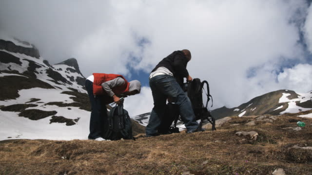 two hikers packing their backpacks