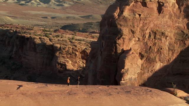 Two hikers walking along narrow sandstone ridge at sunset in desert