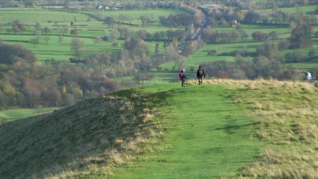 HA WS ZO Two hikers walking on hill, Peak District nr Buxton Derbyshire England