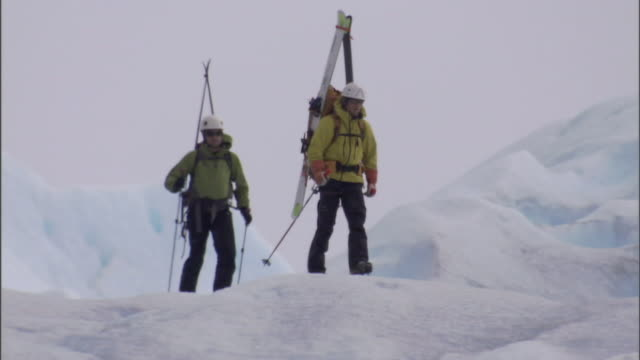 two hikers work their way over the uneven surface of a glacier. - bastoncino da sci video stock e b–roll