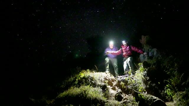 vidéos et rushes de deux voyageurs d'aventure de randonnée sur les montagnes avec le ciel étoilé de nuit - observatoire