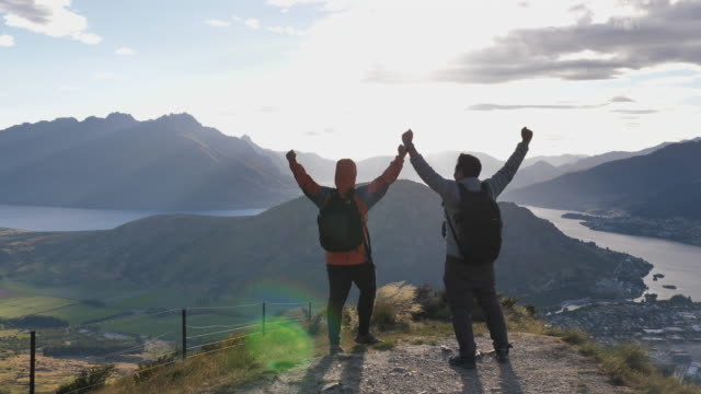 two hiking mountain man on the mountain top raising hands in sunset - at the edge of stock videos & royalty-free footage