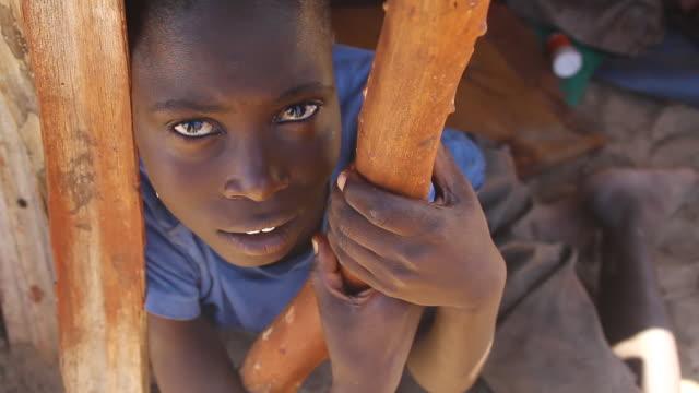 cu two himba boys sitting inside hut / himba, kunene, namibia - wiese点の映像素材/bロール