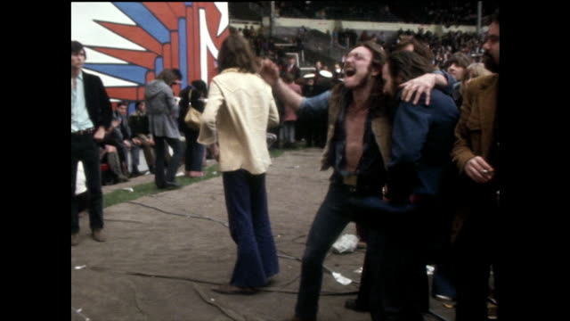 vídeos de stock e filmes b-roll de two hippies dance excitedly at a rock concert; 1972 - jeans