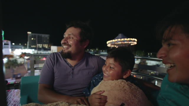 two hispanic brothers and their father ride the ferris wheel at a summer carnival - wilmington north carolina stock-videos und b-roll-filmmaterial