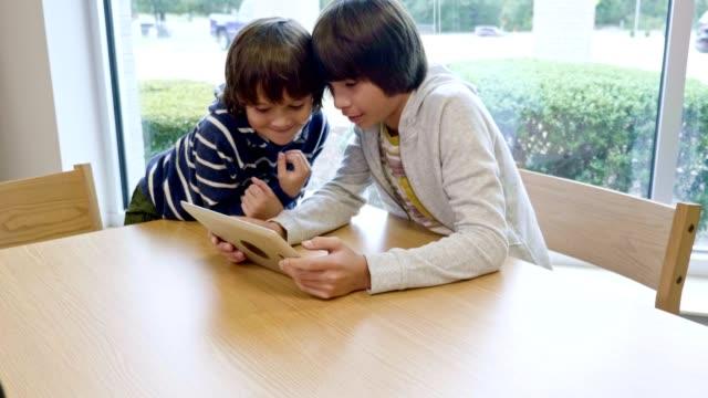 vídeos de stock e filmes b-roll de two hispanic brothers look at digital tablet while in school library - aluna da escola secundária
